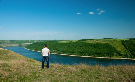 Young man stands on the top of the hill viewing wide Dnister riv
